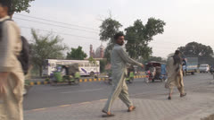 Pakistani Men Walking in front of a Mosque Stock Footage