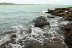 Sea waves hitting round rocks and splashing Stock Photos