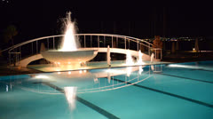Swimming pool with fountain in night illumination Stock Footage