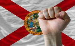 us state flag of florida with hard fist in front of it symbolizing power - stock photo