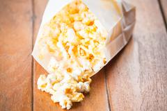 popcorn paper bag opened with corn spilling out - stock photo