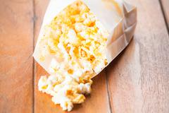 Popcorn pack opened with corn spilling out Stock Photos