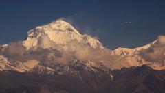 Plane flies against Dhaulagiri peak. - stock footage