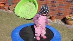 Little girl  is trying to jump on the trampoline Stock Footage
