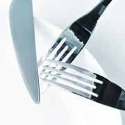 plate, knife and forks on a set table - stock photo