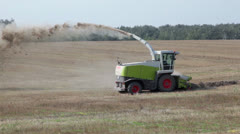 Harvester ride and sow seeds which it collects on verge of field Stock Footage