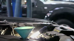 Funnel inserted in tank of car at automobile service station Stock Footage