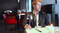 Man holds glass of wine and smells it during he sits at table Stock Footage