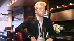 Young man in black suit smiles when sits and wait at bar Stock Footage
