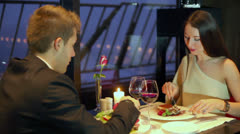 Young woman eats cake and man prefers vegetables at restaurant Stock Footage