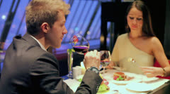 Young man drinks red wine with which woman eats cake Stock Footage