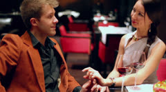 Man takes hand of woman and speak during sit at restaurant Stock Footage