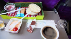 Breakfast food in box on table at plane, (panoramic motion) Stock Footage