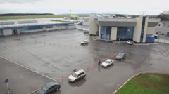 People walk near parking place and buildings of airport Stock Footage