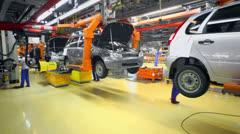 Stock Video Footage of Workers set wheels on car Lada Kalina in Togliatti