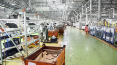 People toil in workshop with car assembly conveyer at factory Stock Footage