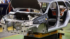 Stock Video Footage of Unfinished car slides on conveyer at workshop in factory