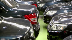Many new cars stand in garage at factory, (shown in motion) Stock Footage