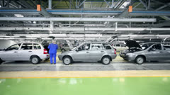 Woman checks Lada Kalina cars which slide on conveyer Stock Footage