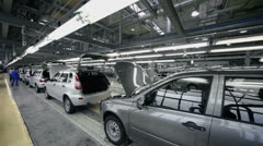 Workers examine new Lada Kalina cars which slide on conveyer Stock Footage