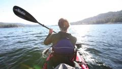 Man kayaks on Alpine lake Stock Footage
