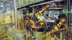 Robotics assemble automobile at conveyer in factory workshop - stock footage