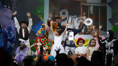 Kids waving on stage with screen behind them at Forum hall Stock Footage