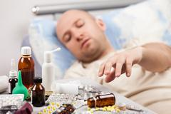 unwell man patient lying down bed - stock photo