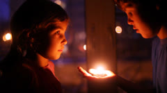 Cute boy and girl stay face to face with candle and talk Stock Footage