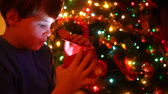 Boy looking into an open box amazed in front of christmas tree Stock Footage