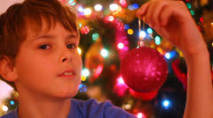 Cute little boy with a globe in his hand near christmas tree Stock Footage