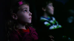 Boy and girl sitting in chair in theater Stock Footage