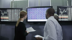 Busy team of financial traders  working together and watching the world markets - stock footage