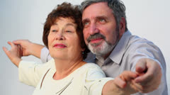 Old man stands behind aged woman and they hold hands aside Stock Footage