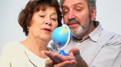 Senior couple hold earth miniature and speak, closeup Stock Footage