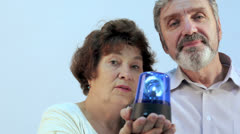 Aged woman with her husband hold blue blinker on hands Stock Footage
