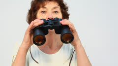 Old woman begins to look in binoculars with orange lenses - stock footage