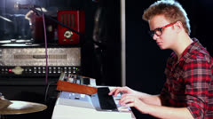 Boy in glasses plays synthesizer in dark studio with mirror wall Stock Footage