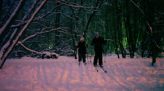 Two kids skiing at forest covered by snow during sunset - stock footage