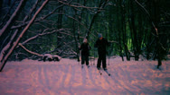 Two kids skiing at forest covered by snow during sunset Stock Footage
