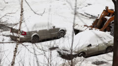 Bulldozer removes snow between two cars on parking at winter day Stock Footage