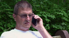 Elderly man on telephone in nature Stock Footage
