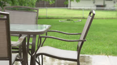 Rain falling on backyard patio furniture slow motion Stock Footage