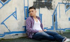 handsome young man sitting against colorful graffiti - stock photo