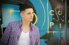 Handsome teenager against colorful graffiti wall Stock Photos