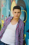 good looking young man against graffiti wall - stock photo