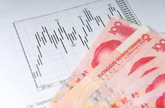 Chinese money with stock chart Stock Photos