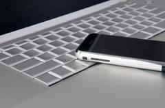 Cell phone on computer laptop Stock Photos