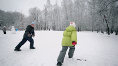 Two kids boy and little girl in warm clothes runs by path Stock Footage