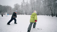 Stock Video Footage of Two kids boy and little girl in warm clothes runs by path